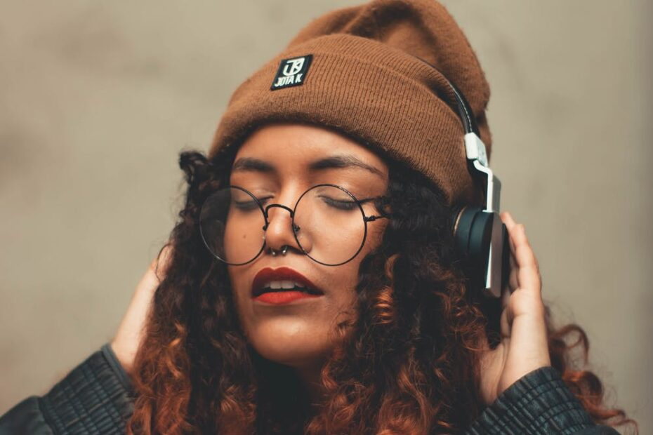 a long-haired person who is listening to music on headphones with their eyes closed